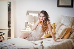 形成挑战的白色短的紧的礼服的年轻美丽的性感的妇女室内在葡萄酒床上 bedr的肉欲的长的头发浅黑肤色的男人 免版税库存照片