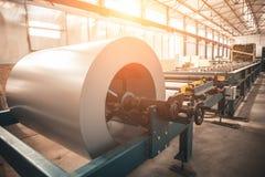形成机器的金属板的工业被镀锌的钢卷卷在金属制品工厂车间,阳光 免版税库存图片
