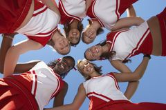 形成杂乱的一团的愉快的啦啦队员 免版税库存照片