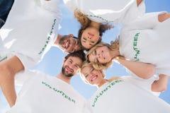 形成杂乱的一团的愉快的志愿者反对蓝天 免版税库存照片