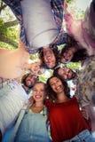 形成杂乱的一团的愉快的朋友在公园 免版税库存图片
