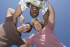 形成杂乱的一团的男性朋友 免版税库存图片