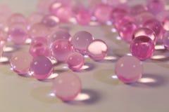形成胶冻在桌上驱散的桃红色透明小珠 免版税库存图片