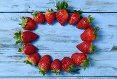 形成蓝色木表面上的草莓一个圈子 免版税库存图片