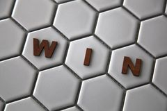 形成词的信件在六角形被塑造的瓦片赢取 免版税图库摄影