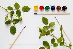 水彩、刷子、纸和玫瑰色花在白色桌书桌被安置 顶视图,平的位置 免版税库存照片