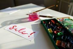 水彩在白色纸片的题字销售,在桌上 免版税图库摄影