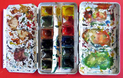 水彩在红色桌上的油漆箱子 库存图片