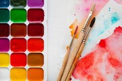 水彩油漆、刷子和纸顶视图调色板w的 图库摄影