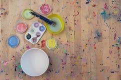 水彩油漆、油漆刷和一个白色碗在淡色 免版税库存图片