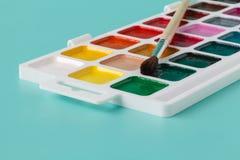 水彩油漆和刷子在白色箱子,在蓝色背景 图库摄影