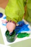 水彩油漆版本记录在child& x27的; 在纸的s手 库存照片