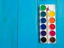 水彩油漆调色板在蓝色木背景的 库存图片