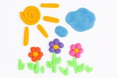 彩色塑泥太阳、天空、云彩和花 免版税库存图片