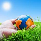彩色塑泥的地球在手上 免版税库存照片