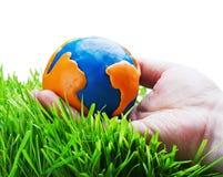 彩色塑泥的地球在手上 库存照片