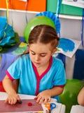 从彩色塑泥的女孩模子在幼儿园 免版税库存图片
