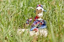 彩色塑泥绵羊坐在草的一个岩石 免版税库存图片