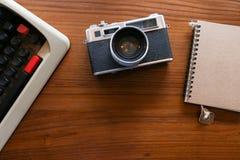 彩色片照相机和葡萄酒古色古香的打字机有笔记本的-顶视图与拷贝空间 免版税库存图片