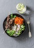 彩虹力量菩萨碗 亚洲样式牛肉串,米细面条,泡菜沙拉红萝卜,黄瓜,萝卜,绿色 免版税库存照片