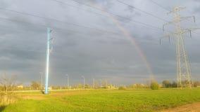 彩虹和电线定向塔的 免版税库存图片