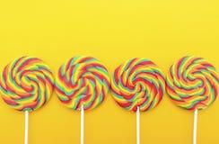 彩虹在明亮的黄色木桌上的棒棒糖糖果 免版税库存图片