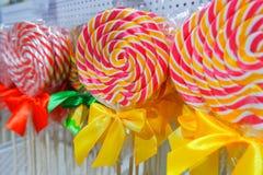 彩虹在木棍子的棒棒糖漩涡在糖果店,选择聚焦 甜糖果 r 棒棒糖在街道的销售中关闭  免版税库存图片