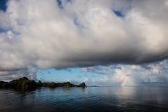 彩虹在王侯的Ampat石灰石海岛附近形成 免版税图库摄影