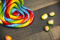 彩虹棒棒糖和橘子果酱在木背景特写镜头 库存图片