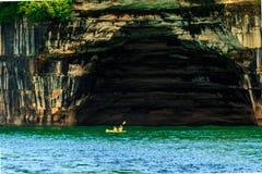 彩虹洞穴的皮艇在湖岸被生动描述的岩石国民 免版税图库摄影