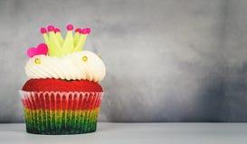 彩虹爱心脏在灰色的国王杯形蛋糕 库存照片