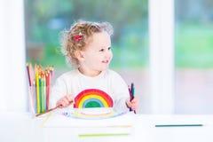 画彩虹的愉快的微笑的小孩女孩 免版税图库摄影