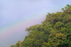 彩虹美好的场面在绿色山的与蓝天在秋天 免版税库存图片