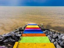 彩虹颜色楼梯到海里 免版税库存照片