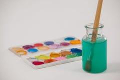 水彩调色板和油漆刷有蓝色油漆的被浸洗入瓶子用水填装了 图库摄影