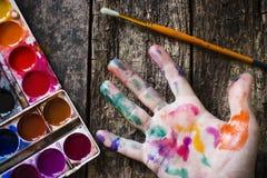 水彩绘艺术家的手的画笔多彩多姿的油漆的在木头 免版税库存图片