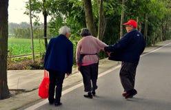 彭州,中国:乡下公路的三个老年人 免版税库存照片