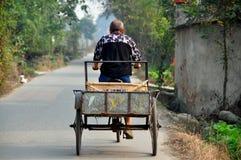 彭州,中国:农夫贩卖他的沿乡下公路的自行车推车 免版税库存图片