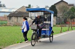 彭州,中国:在乡下公路的Pedicab出租汽车 库存照片