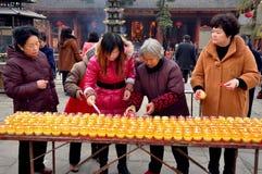 彭州,中国:点燃蜡烛的妇女 库存图片
