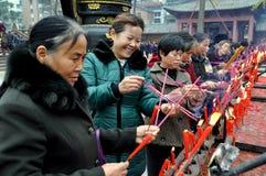 彭州,中国:点燃香火棍子的妇女 库存图片