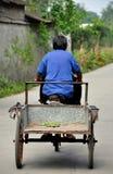 彭州,中国:驾驶自行车推车的年长妇女 库存图片