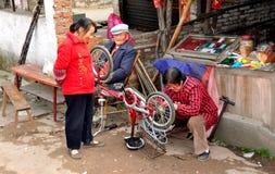 彭州,中国: 修理自行车的妇女 图库摄影