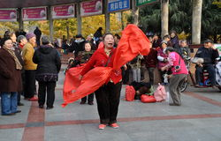 彭州,中国: 唱歌与红色丝绸的妇女 图库摄影