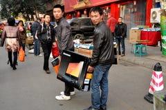 彭州,中国: 运载Lenovo计算机的二个人 免版税库存图片
