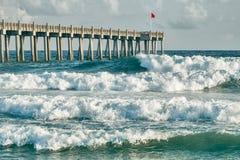 彭萨科拉海滩渔码头的海浪的 库存照片