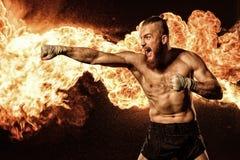影子拳击与火和火花的专业战斗机在背景 库存照片