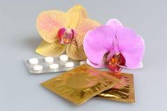 影片上漆的片剂,有两朵兰花花的避孕套在灰色 免版税库存照片