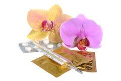 影片上漆的片剂,避孕套,有两朵兰花花的温度计 免版税库存照片