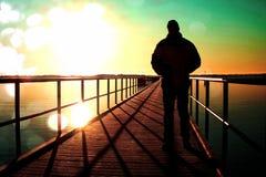 影片五谷 人在码头建筑的剪影步行在太阳的海上 与清楚的天空的意想不到的早晨,光滑的水平面 免版税库存照片